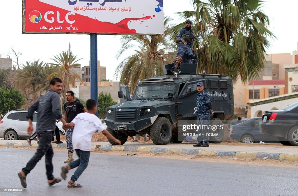 Libyan demonstrators run for cover from shelling during a protest in the eastern coastal city of Benghazi calling for military forces to re-capture the southern city of Sirte from the Islamic State (IS) group without foreign intervention on May 6, 2016. The head of Libya's unity government announced plans the previous month for a concerted campaign to drive the Islamic State group out of the North African country, but without foreign intervention. The unity government fears that separate operations in Sirte could spark clashes between the multitude of different fighting forces in Libya and play into the jihadists' hands / AFP / ABDULLAH