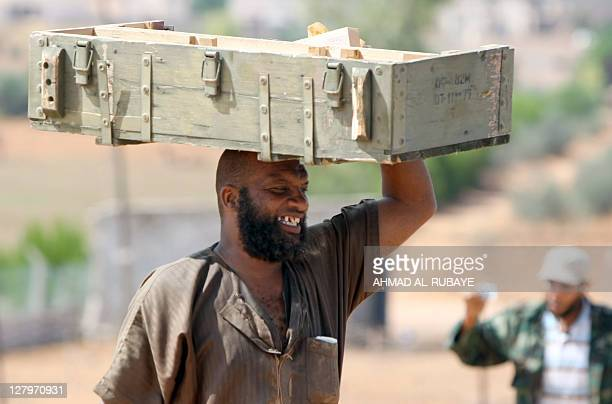 A Libyan fighter carries a crate of ammunition from a farm in the village of Qasr Abu Hadi on the outskirts of the city of Sirte on October 4 2011...