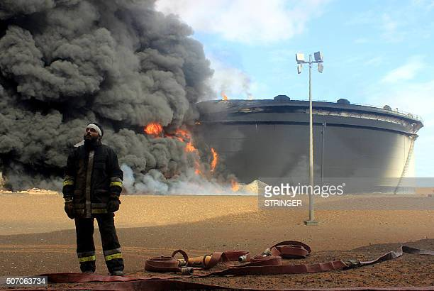 A Libyan fireman stands in front of smoke and flames rising from an oil storage tank at an oil facility in northern Libya's Ras Lanouf region on...