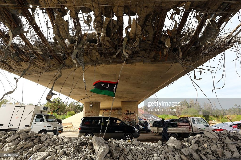 A Libyan flag flutters as cars wait under a bridge on September 9 2014 at a police checkpoint erected on a main road near a former army camp where...