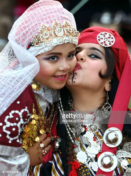 A Libyan girl dressed in a traditional outfit kisses her friend as they attend a school event in the Tajoura area in the capital Tripoli on April...