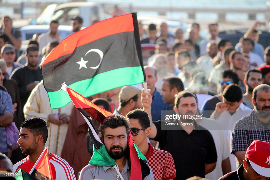 A libyan holds national flag during the protest against the newly elected parliament on August 8 2014 in Benghazi Libya The parliament elected on...