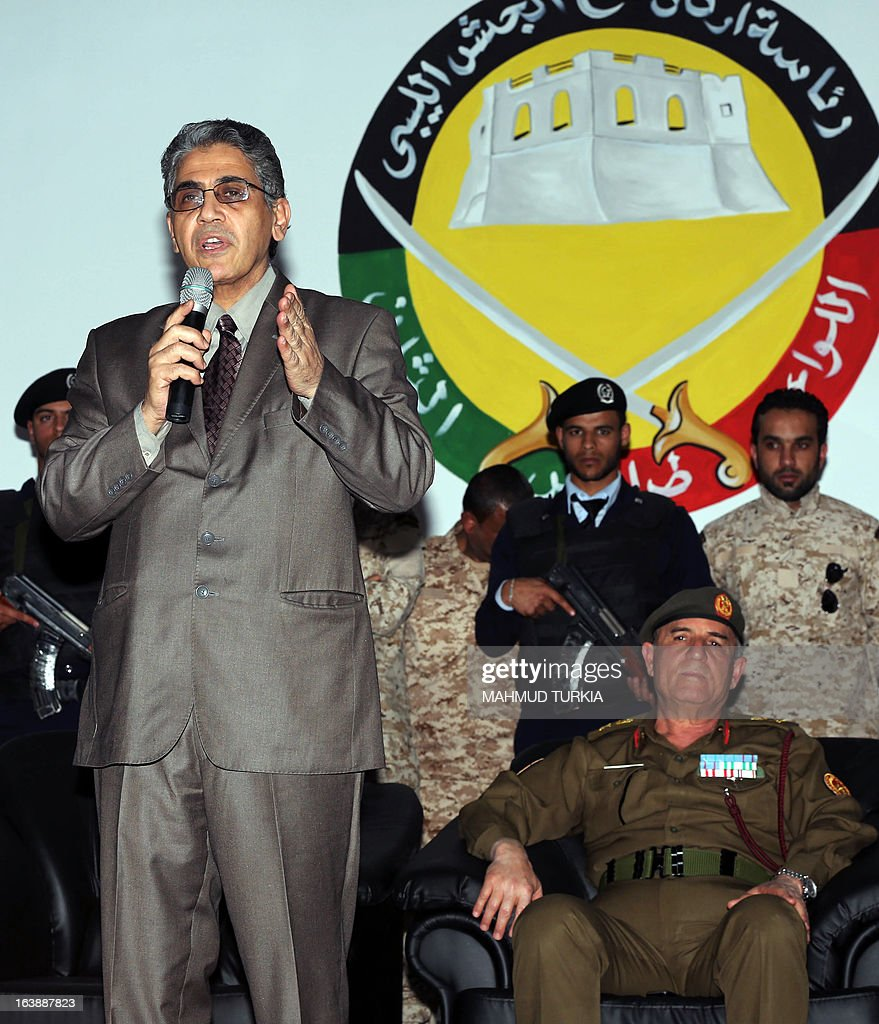 Libyan Interior Minister Ashour Shuail speaks as Libyan Army Chief of Staff Yusef Mangush (seated) listens on, as he announces the start of a campaign to dislodge armed groups illegally occupying more than 500 privately owned or state-owned buildings on March 17, 2013, in the capital Tripoli. The campaign will also include properties outside of the capital.