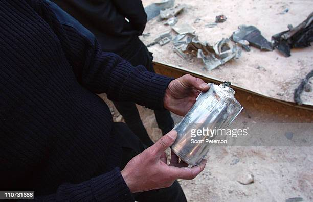 Libyan man holds the lithium thermal battery of a Tomahawk missle as Libyans inspect damage to sheds full of missile training and maintenance...