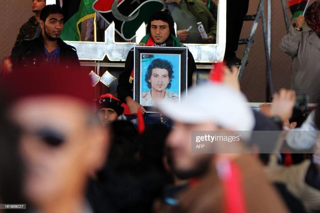 A Libyan man holds the portrait of a man killed during the revolution as hundreds of Libyans celebrate the second anniversary of the Libyan uprising at Tahrir Square on February 17, 2013 in Benghazi. Security forces were on high alert across Libya on Sunday as the north African nation marked two years since the start of the revolt that toppled Moamer Kadhafi after four decades of iron rule. The anniversary of the uprising that ended with Kadhafi's killing in October 2011 comes as Libya's new rulers battle critics calling for a 'new revolution' and accusing them of failing to usher in much-needed reforms.