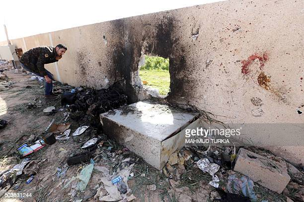 A Libyan man inspect the site of a suicide truck bombing on a police school in Libya's coastal city of Zliten some 170 kilometres east of the capital...