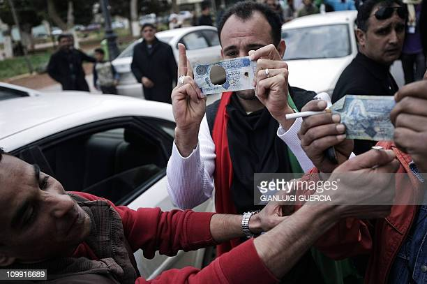 A Libyan man shows a one dinar bill from whitch he cuted out the portrait of Libyan strongman Moamer Kadhafi during an antigovernment demonstration...