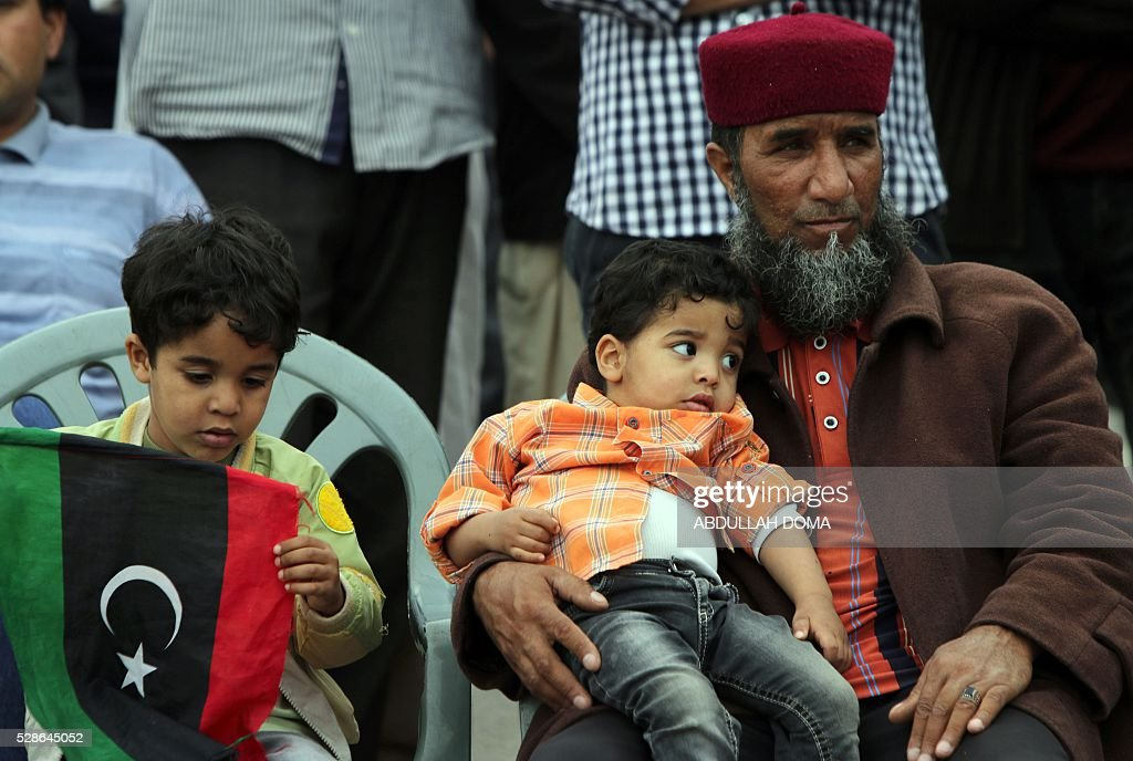 A Libyan man sits with his children, one of whom is holding the country's national flag, during a protest in the eastern coastal city of Benghazi calling for military forces to re-capture the southern city of Sirte from the Islamic State (IS) group without foreign intervention on May 6, 2016. The head of Libya's unity government announced plans the previous month for a concerted campaign to drive the Islamic State group out of the North African country, but without foreign intervention. The unity government fears that separate operations in Sirte could spark clashes between the multitude of different fighting forces in Libya and play into the jihadists' hands / AFP / ABDULLAH