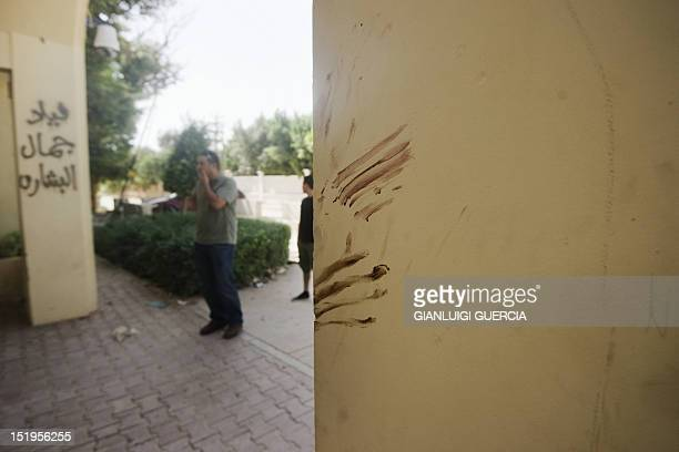 A Libyan man stands next to a wall apparently stained with blood at the main entrance of the US consulate in Benghazi on September 13 following an...