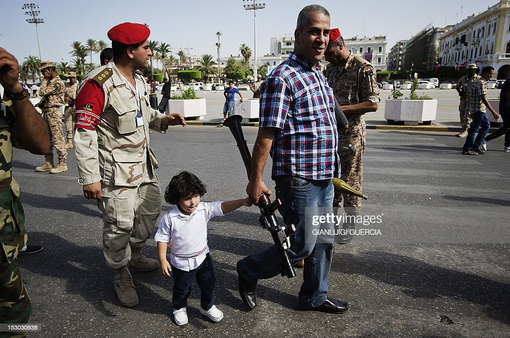 A Libyan man walks with his child while carrying a rocket-propelled grenade launcher to be handed over during a ceremony at Martyrs' Square in Tripoli on September 29, 2012. Hundreds of Libyans handed over weapons to the military in Tripoli and the eastern city of Benghazi as Libya's new leadership began to take steps to tackle militias, in the wake of massive anti-militia protests.
