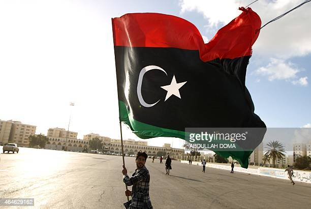 A Libyan man waves his national flag as protesters gather for a demonstration calling on the international community to lift the ban on arming or...