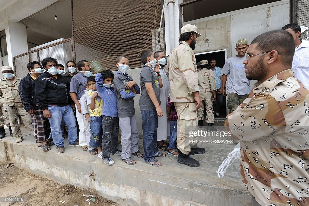 Libyan men and children queue to have a look at the corpses of Libya's ex-strongman Moamer Kadhafi and his son Mutassem, displayed inside the cold storage room of a vegetable market near a mosque on the outskirts of Misrata on October 22, 2011. Military commanders in the Libyan city of Misrata said that no post-mortem would be carried out on the body of Kadhafi despite concerns over how the toppled dictator died. AFP PHOTO/PHILIPPE DESMAZES