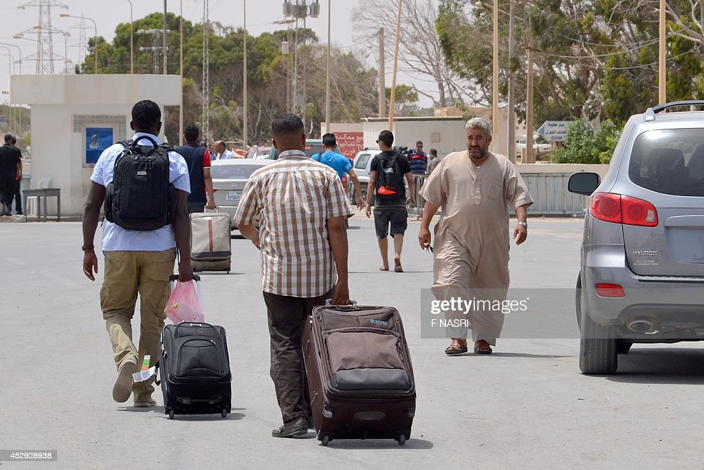 Libyan men fleeing the violence in their country enter Tunisia through the southern border crossing at Ras Jedir on July 30, 2014. Tunisia cannot cope with any massive influx of refugees who might seek to enter the country from strife-torn neighbouring Libya and will close its border if necessary, the foreign minister said.