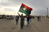 Libyan men wave their national flag during a demonstration marking the fifth anniversary of the Libyan revolution which toppled strongman Moamer...