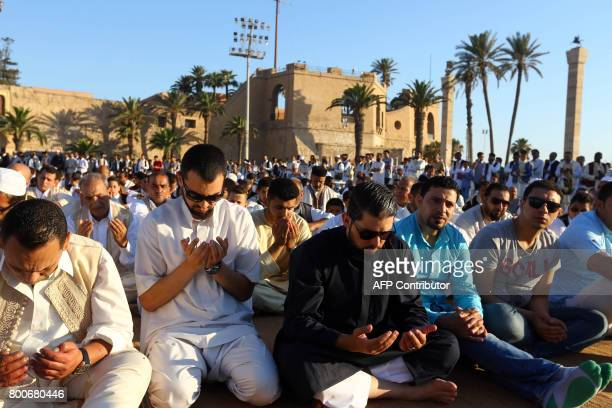 Libyan Muslim worshippers perform Eid alFitr prayers at the Martyrs' Square in the capital Tripoli on June 25 2017 to mark the end of the fasting...