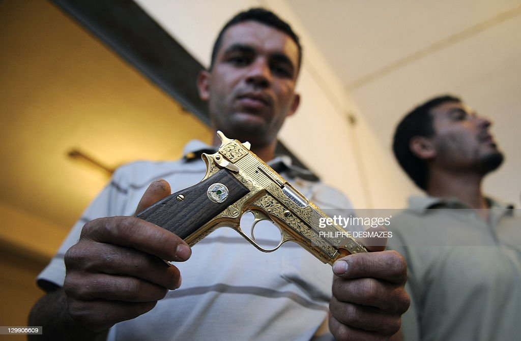 Libyan National Transitional Council (NTC) fighter Nabil Ali Dagouich shows on October 21, 2011 in the flashpoint city of Misrata Moamer Kadafhi's golden gun after participating in the capture of Libya's late strongman the day before. AFP PHOTO/PHILIPPE DESMAZES