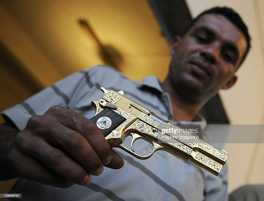 Libyan National Transitional Council (NTC) fighter Nabil Ali Dagouich shows at a farm in Misrata on October 21, 2011 Moamer Kadafhi's golden gun after participating in the capture of Libya's late strongman the day before. The fighters at a farm on the outskirts of the city of Misrata that serves as their Al-Ghiran brigade base proudly exhibit the ousted leader's black boots, gold-plated gun and beige scarf. AFP PHOTO/PHILIPPE DESMAZES