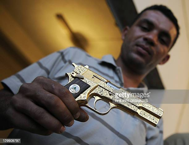 Libyan National Transitional Council fighter Nabil Ali Dagouich shows at a farm in Misrata on October 21 2011 Moamer Kadafhi's golden gun after...