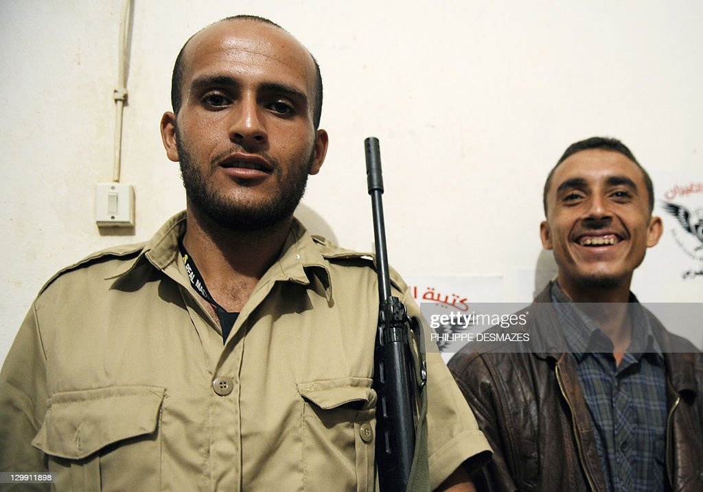 Libyan National Transitional Council (NTC) fighters Ahmed Mohamed Gazal (L) and Ghiran Shaaban (R) pose at a farm in Misrata on October 21, 2011 after participating in the capture of Libya's late strongman Moamer Kadhafi the day before. The fighters proudly exhibit the ousted leader's black boots, gold-plated gun and beige scarf at the farm on the outskirts of the flashpoint city that serves as their Al-Ghiran brigade base. AFP PHOTO/PHILIPPE DESMAZES