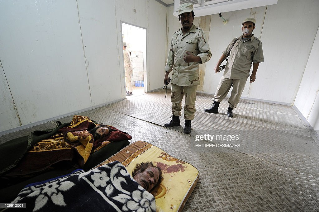 Libyan National Transitional Council (NTC) fighters stand guard next to the corpses of Libya's ex-strongman Moamer Kadhafi (R) and his son Mutassem, displayed inside the cold storage room of a vegetable market near a mosque on the outskirts of Misrata on October 22, 2011. Military commanders in the Libyan city of Misrata said that no post-mortem would be carried out on the body of Kadhafi despite concerns over how the toppled dictator died. AFP PHOTO/PHILIPPE DESMAZES