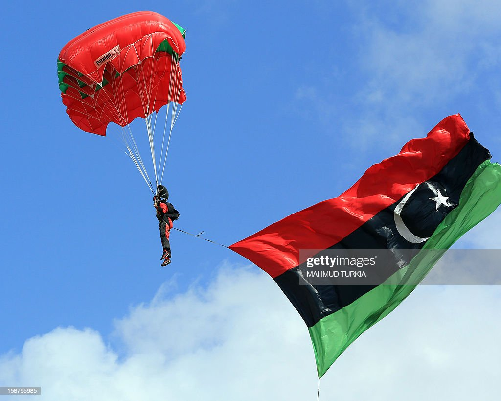 A Libyan parachutist with the new national flag attached to his legs drops through the sky into the capital Tripoli during the first sports festival marking the 61st anniversary of Libya's Independence, on December 29, 2012. AFP PHOTO/MAHMUD TURKIA
