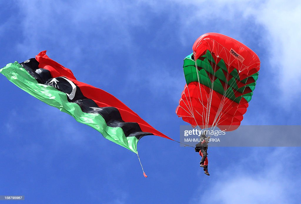 A Libyan parachutist with the new national flag attached to his legs drops through the sky into the capital Tripoli during the first sports festival marking the 61st anniversary of Libya's Independence, on December 29, 2012.