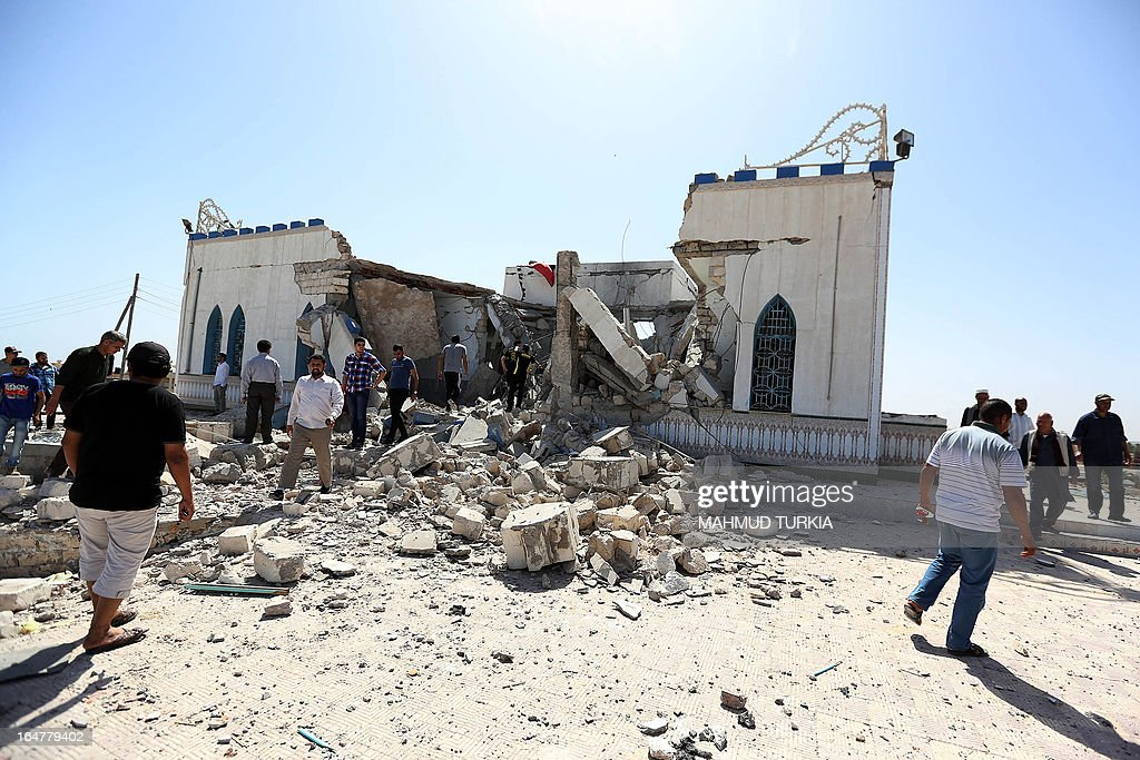 Libyan people walk through the debris and rubble of a damaged Sufi shrine in the neighbourhood of Tajoura, on the outskirts of Tripoli, after it was attacked during the early hours of the morning by unknown individuals on March 28, 2013. Unknown attackers planted and set off an explosive device, partially destroying the mausoleum of Sidi Mohamed Landoulsi, a 15th Century Sufi Theologist.