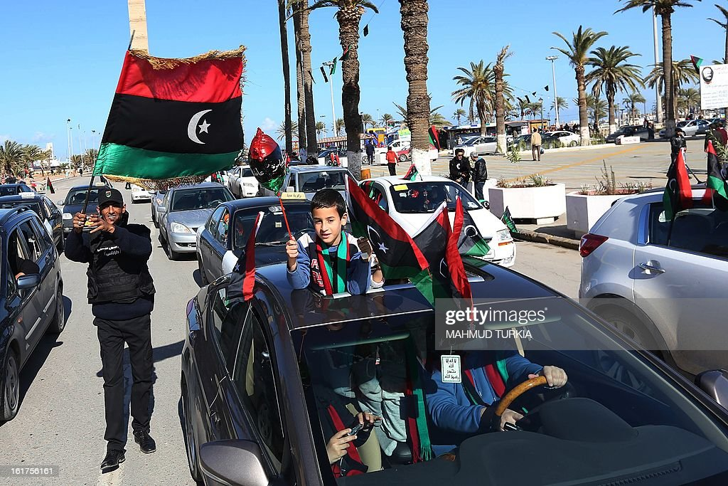 Libyan people wave flags near the Martyrs square as they celebrate, two days ahead of the second anniversary of the uprising that toppled the regime of strongman Moamer Kadhafi on February 15, 2013 in Tripoli. The government has already taken a series of measures to contain any attempt by supporters of the former regime to 'sow chaos' amid anger from protesters who accuse the new rulers of failing to push for reform.