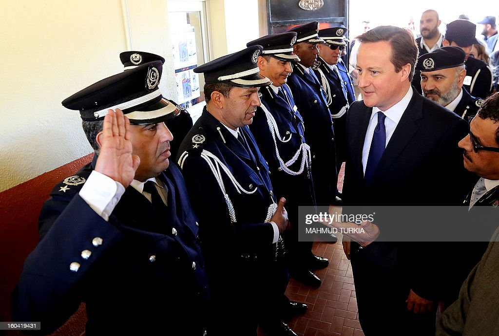 A Libyan police officer salutes British Prime Minister David Cameron (R) upon his arrival to attend a graduation ceremony for Police Officers as part of a visit in Libya on January 31, 2013 in Tripoli. Cameron does a surprise visit in Libya following a one-day-visit in Algeria in the wake of this month's hostage crisis in the Sahara in which several Britons were killed.