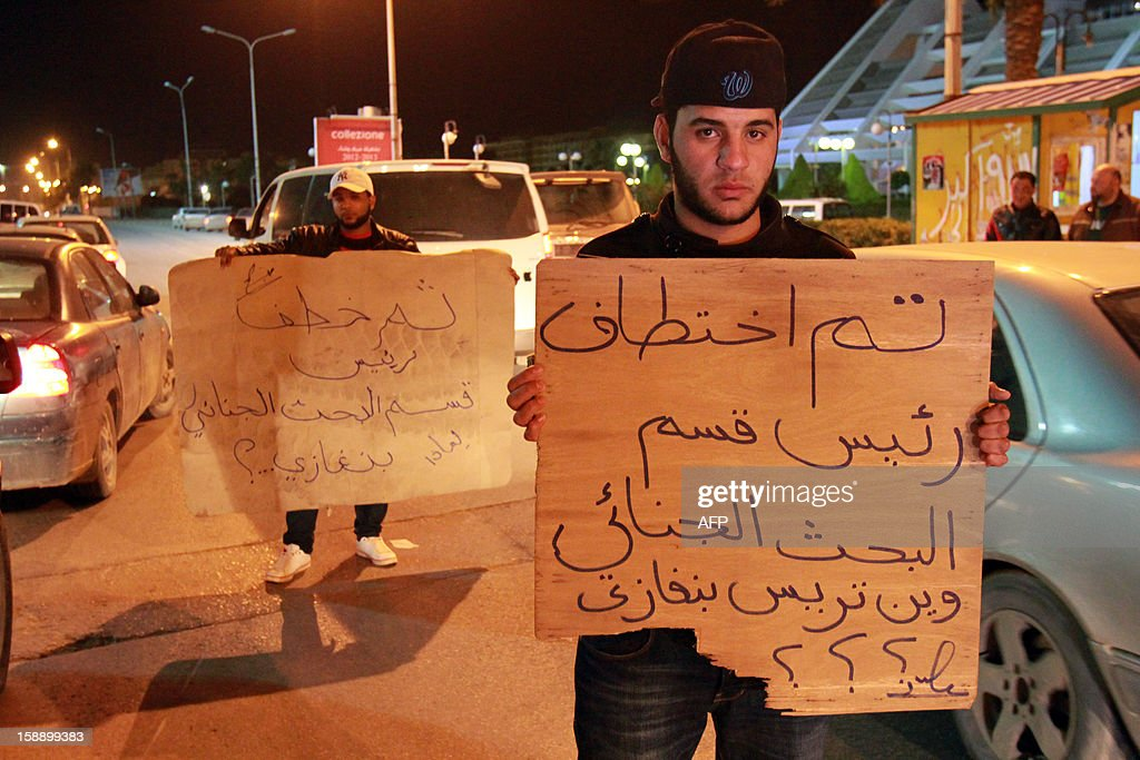 Libyan policemen in civilian clothing protest against the kidnapping of the Head of Criminal Investigation Department, Abdel Salam al-Mahdawi, outside the Tibesti hotel in Benghazi, on January 3, 2013. An unidentified armed group kidnapped Mahdawi on the eve of January 2, according to an official security source confirmed to Agence France Presse. Arabic writing on placard reads 'The Head of Criminal Investigation Department was kidnapped, where are the men of Benghazi?'