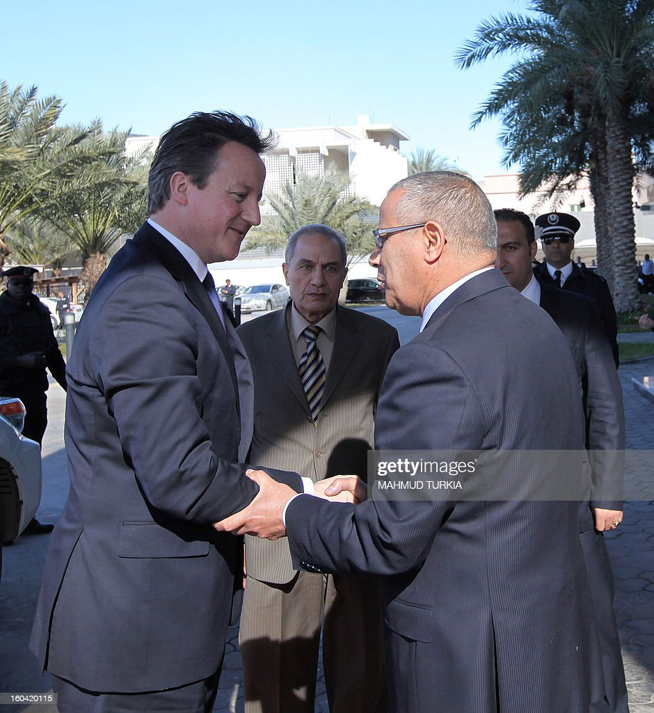 Libyan prime minister Ali Zaidan (R) greets British Prime Minister David Cameron (L) ahead of their meeting as part of the British PM visit in Libya on January 31, 2013 in Tripoli. Cameron does a surprise visit in Libya following a one-day-visit in Algeria in the wake of this month's hostage crisis in the Sahara in which several Britons were killed.