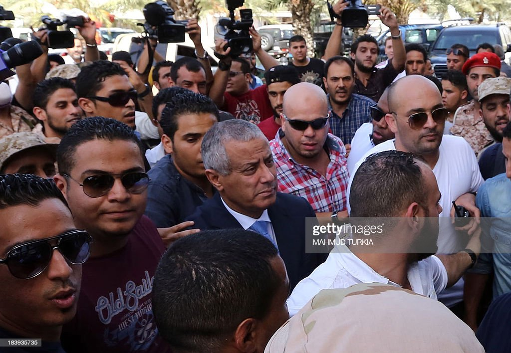 Libyan Prime Minister <a gi-track='captionPersonalityLinkClicked' href=/galleries/search?phrase=Ali+Zeidan&family=editorial&specificpeople=7544817 ng-click='$event.stopPropagation()'>Ali Zeidan</a> (C) arrives at the government headquarters in Tripoli on October 10, 2013 shortly after he was freed from the captivity of militiamen who had held him for several hours. Gunmen seized Zeidan from a hotel, where he resides, in the Libyan capital and held him for several hours before he was freed, in the latest sign of Libya's lawlessness since Moamer Kadhafi was toppled in 2011. AFP PHOTO / MAHMUD TURKIA