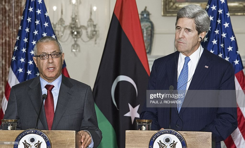Libyan Prime Minister Ali Zeidan delivers remarks to the media as US Secretary of State John Kerry listens on his translation headsets after their private bilateral meeting March 13, 2013, at the US Department of State in Washington, DC. AFP Photo/Paul J. Richards