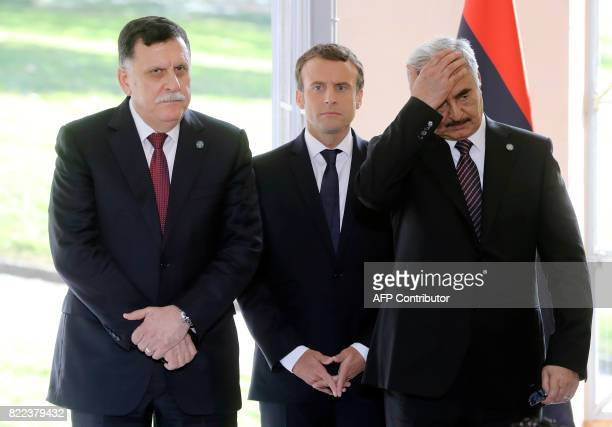 Libyan Prime Minister Fayez alSarraj French President Emmanuel Macron and General Khalifa Haftar commander in the Libyan National Army give a press...