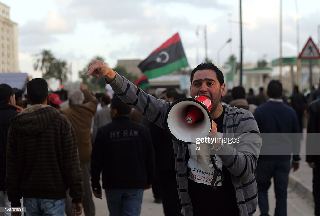 A Libyan protester shouts slogans with a megaphone during a demonstration in the eastern city of Benghazi on December 28, 2012 to demand that militias made up of former rebels who helped oust dictator Moamer Kadhafi disband and join the army and police.