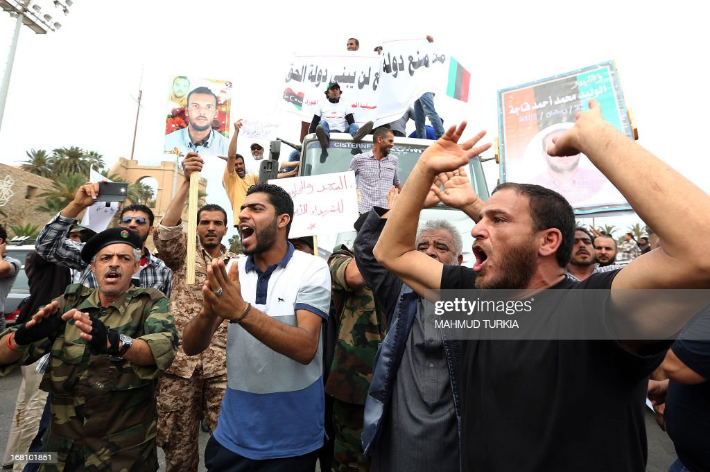 Libyan protesters hold placards and banners during a demonstration in support of the 'political isolation law' in Libya's landmark Martyrs Square on May 5, 2013 in Tripoli, Libya. Libya's General National Congress, under pressure from armed militias, voted through a controversial law to exclude former regime officials from government posts. Gunmen who had surrounded the foreign and justice ministries to press for officials from the regime of the late dictator Moamer Kadhafi to be sacked from top government jobs lifted the sieges when state television broke the news.