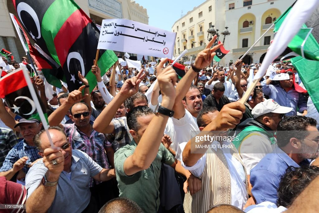 Libyan protesters shout slogans waving national flags during a demonstration on the Algeria Square to demand the removal of arms and the evacuation of unofficial armed groups and the implementation of the General National Congress (GNC)'s decision on July 7, 2013 in the Libyan capital Tripoli. The GNC, the country's highest political authority, announced last June his decision to remove 'illegal militias' from the capital after deadly fightings that highlighted the lack of security nearly two years after dictator Moamer Kadhafi fell.