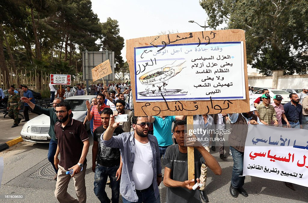 Libyan protesters wave banners as they demonstrate outside the Libyan General National Congress in support of the 'Political Isolation Law' which calls for the expulsion of former regime employees from top government and political posts on April 30, 2013 in Tripoli. Armed men demanding the expulsion of former officials of the regime of ousted Libyan leader Moamer Kadhafi surrounded the justice ministry in the capital, widening a campaign that began on the weekend with a siege on the foreign ministry, an official said. AFP PHOTO/MAHMUD TURKIA