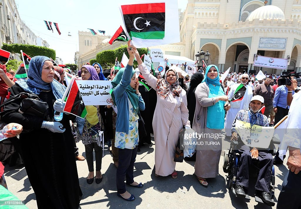 Libyan protesters wave national flags and hold placards during a demonstration on the Algeria Square to demand the removal of arms and the evacuation of unofficial armed groups and the implementation of the General National Congress (GNC)'s decision on July 7, 2013 in the Libyan capital Tripoli. The GNC, the country's highest political authority, announced last June his decision to remove 'illegal militias' from the capital after deadly fightings that highlighted the lack of security nearly two years after dictator Moamer Kadhafi fell.