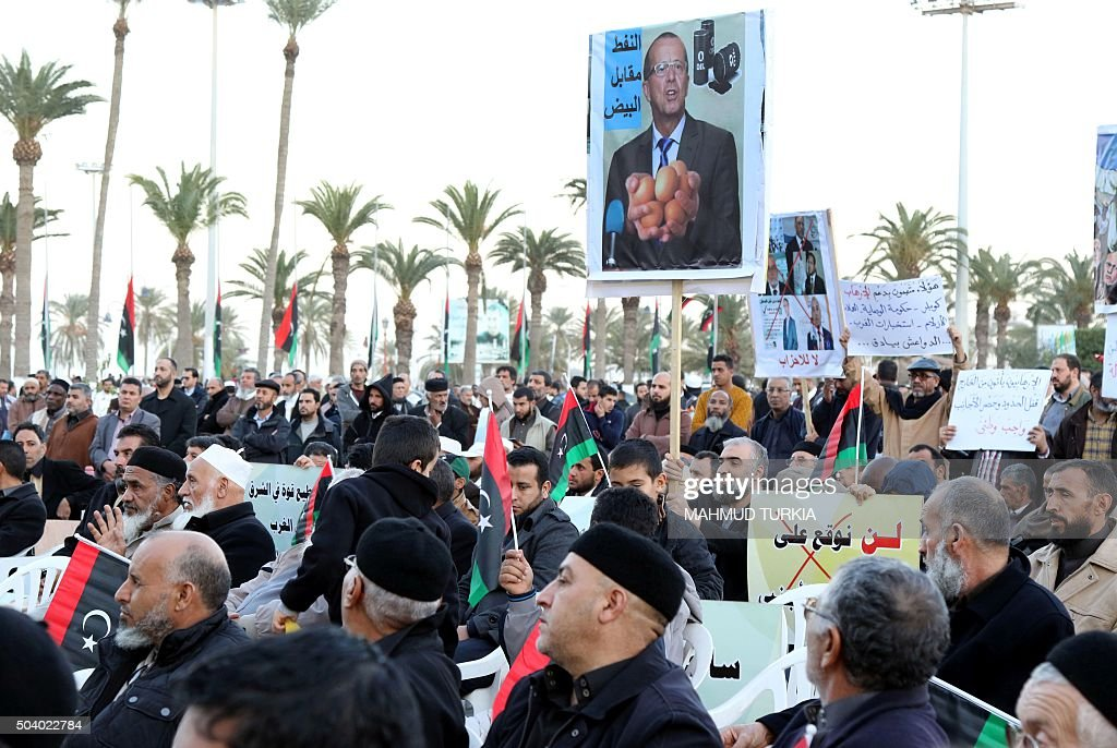 Libyan protesters wave their national flags and placards bearing portraits of UN envoy for Libya Martin Kobler during a demonstration against a...