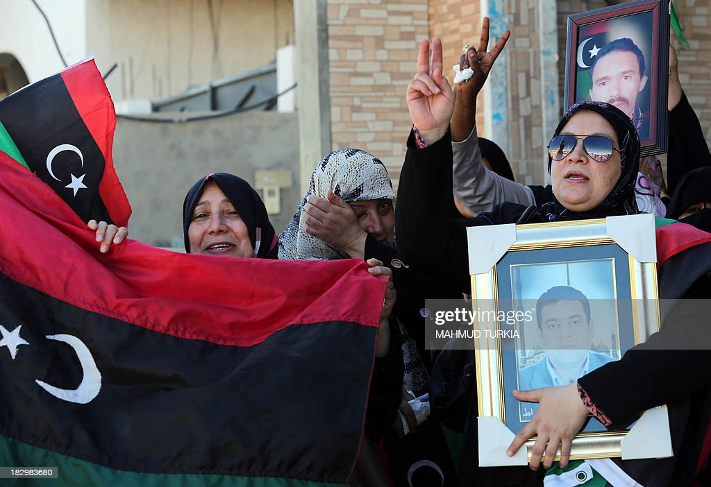 Libyan protestors flash the sign for victory and hold pictures of killed relatives and their national flag as they demonstrate outside the court in Tripoli against Libya's ex-intelligence chief Senussi Baghdadi al-Mahmudi, the last prime minister to serve under slaine leader Moamer Kadhafi, accused of crimes during the 2011 revolt, during his pre-trial hearing, on October 3, 2013. The Tripoli court will decide October 24 whether to indict more than 20 senior figures from Kadhafi's regime charged with killing protesters during the 2011 revolt that toppled him.