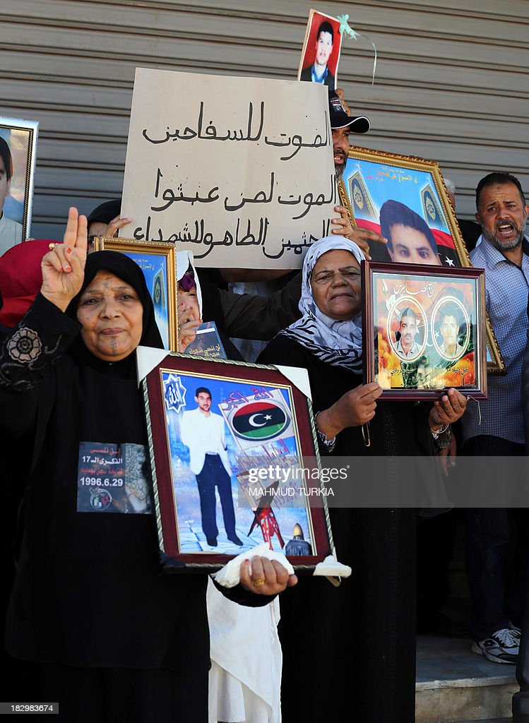 Libyan protestors hold pictures of killed relatives as they demonstrate outside the court in Tripoli against Libya's ex-intelligence chief Senussi Baghdadi al-Mahmudi, the last prime minister to serve under slaine leader Moamer Kadhafi, accused of crimes during the 2011 revolt, during his pre-trial hearing, on October 3, 2013. The Tripoli court will decide October 24 whether to indict more than 20 senior figures from Kadhafi's regime charged with killing protesters during the 2011 revolt that toppled him.