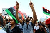 Libyan protestors wave their national flag and shout slogans during a rally in central Tripoli's Martyr's Square on September 12 2014 in support of...