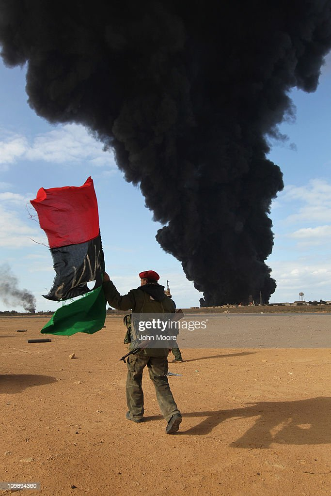 A Libyan rebel carries an independence-era Libyan flag as a facility burns during fighting on the frontline on March 9, 2011 near Ras Lanuf, Libya. The rebels pushed back government troops loyal to Libyan leader Muammar Gaddafi towards Ben Jawat.