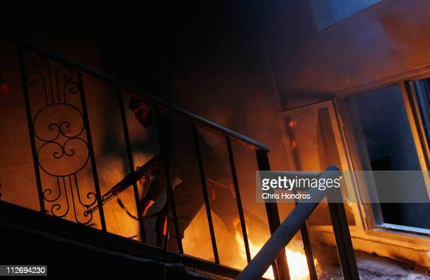 A libyan rebel fighter runs up a burning stairwell during an effort to dislodge some ensconced government loyalist troops who were firing on them...