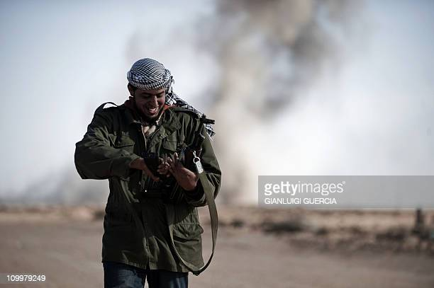 A Libyan rebel fighter smiles while changing his gun magazine as smoke raises from a bomb dropped by a Libyan jet fighter on the outskirt of the...