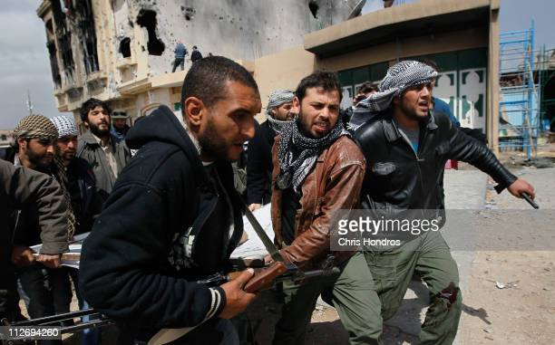 Libyan rebel fighters carry out a comrade wounded during an effort to dislodge some ensconced government loyalist troops who were firing on them from...