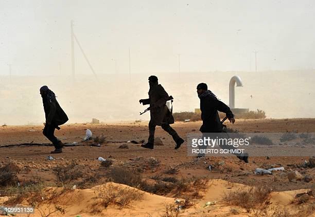 Libyan rebel fighters run to give assistance to their comrades after a Kadhafi loyalist Airforce fighter jet dropped a bomb near by on March 11 2011...