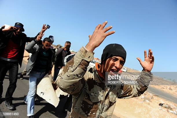 Libyan rebel fighters shout while carrying the body of comrade killed by a bomb dropped by a Kadhafi loyalist Airforce fighter jet on March 11 2011...