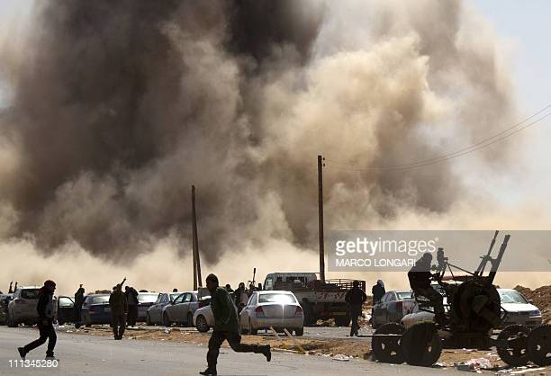 Libyan rebel fighters take cover as a bomb dropped by an airforce fighter jet explodes near a checkpoint on the outskirts of the oil town of Ras...